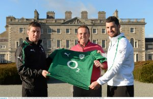 Fly-half Ronan O'Gara (left) and full-back Rob Kearney (right) present Shane Lowry with a rugby shirt signed by the Ireland team.